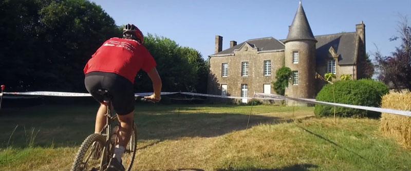 un homme de dos fait du vélo en direction d'un manoir le tout dans un cadre bucolique
