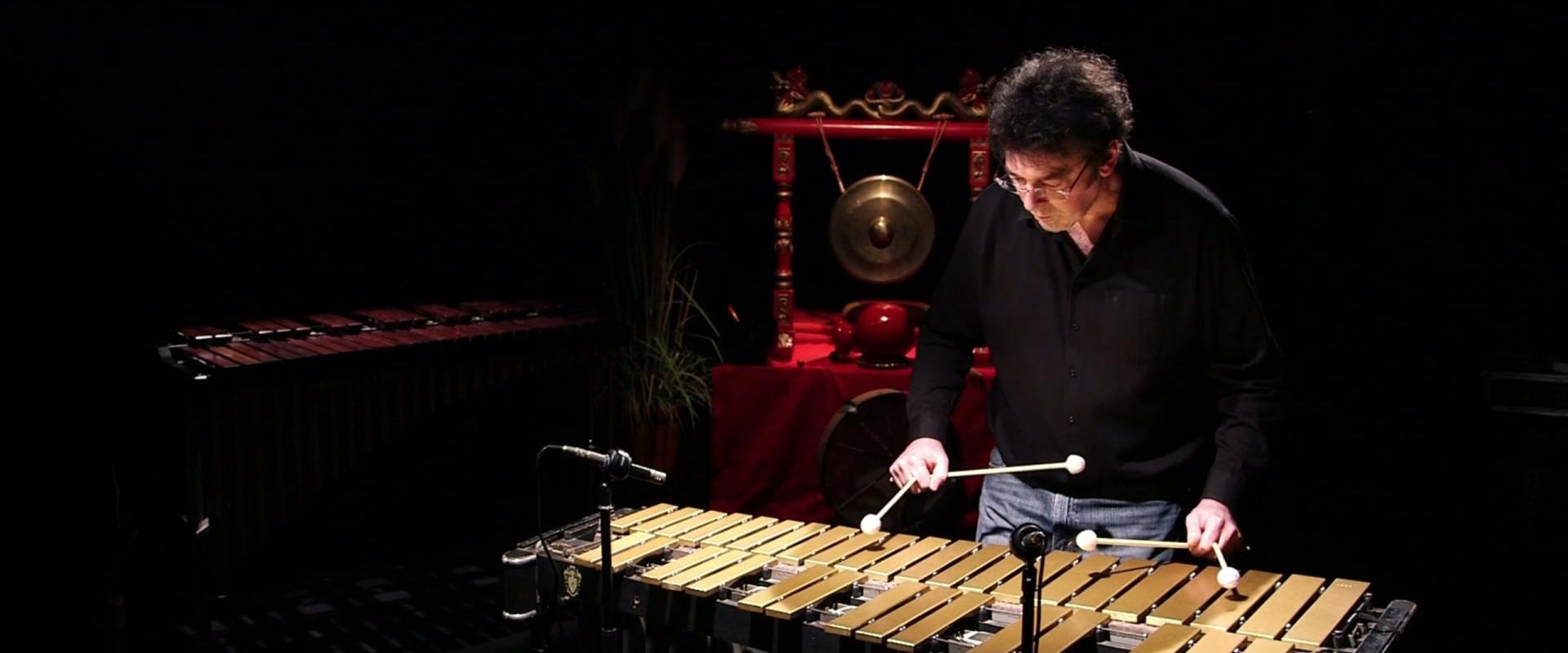 Un homme joue du vibraphone sur un plateau d'enregistrement, on aperçoit un bong indonésien en fond de scène