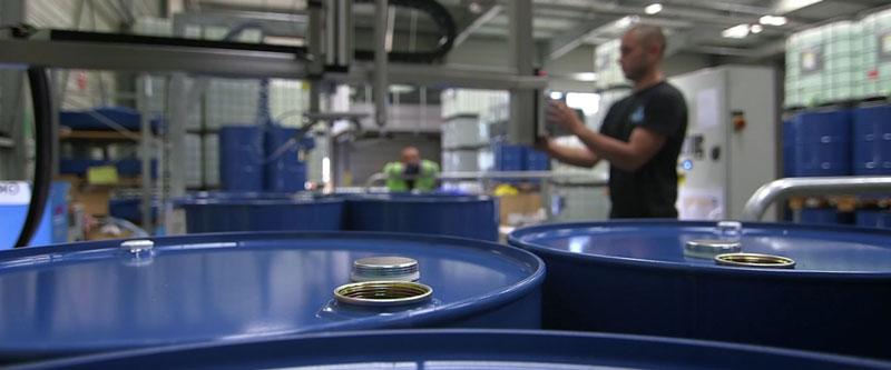 Dans un entrepôt, un technicien remplit des bidons